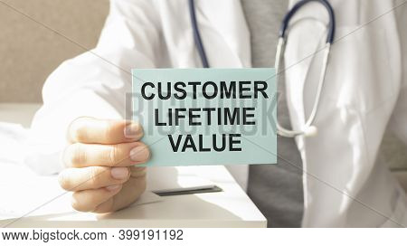 Closeup On Businessman Holding A Card With Text Customer Lifetime Value, Business Concept Image With
