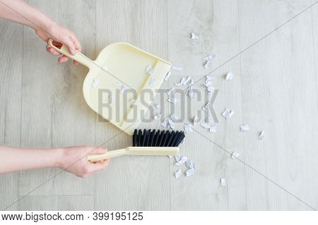 The Hands Of A Caucasian Woman Removes Rubbish From The Floor With A Brush And Scoop.