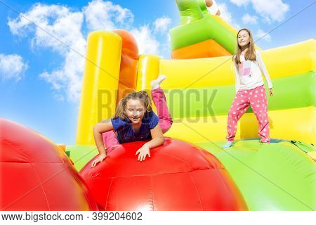 Happy Little Girls Having Lots Of Fun While Jumping From Ball To Ball On An Inflate Castle.