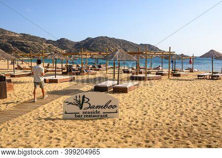 Ios, Greece - September 20, 2020: Seaside Bar Restaurant With Sun Loungers And Umbrellas On Mylopota