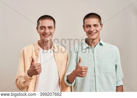 Portrait Of Two Young Happy Twin Brothers Showing Thumb Up And Smiling At Camera While Posing Togeth