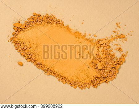 Top View Of Smudged Eyeshadow Sample Toned In Trendy Marigold Colour. Makeup And Cosmetics Backgroun