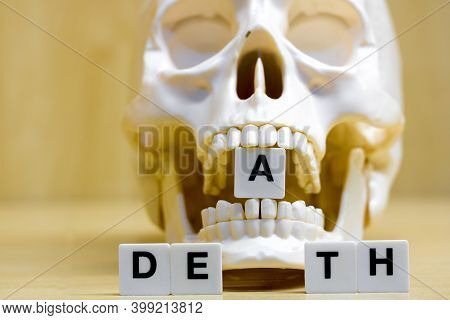 A Row Of Small White Plastic Tiles, Containing The Letters Forming The Word Death, Placed On A Table