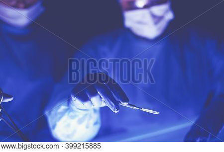 Cropped Picture Of Scalpel Taken Doctors Performing Surgery.