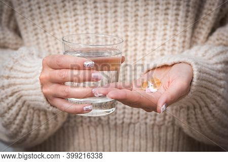 Closeup Of Woman Hands Holding Glass Of Water And Vitamins And Medication. Taking Vitamins And Suppl