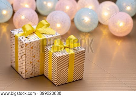 Christmas And New Year's Gifts Are Wrapped In Shiny Paper, With Lighted Lanterns In The Background.