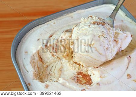 Closeup Of A Spoon Scooping Delectable Caramel Macadamia Nut Ice Cream In The Tub