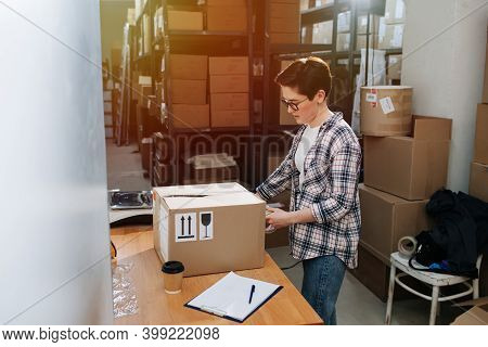 Busy Female Warehouse Worker Closing Box With Cello Tape, Sealing It