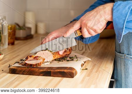 Unrecognizable Man Cuting With Large Knife Baked Pork Tenderloin On Cutting Board On Itchen Table At