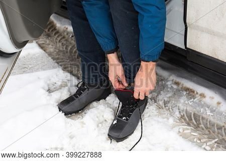 A Man Ties His Ski Boots Before Walking Through The Snow On Cross-country Skis. Shoelaces, Sports Eq