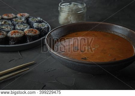 A Bowl Of Soup Tom Yam. Set Of Sushi And A Jar Of Rice On The Background