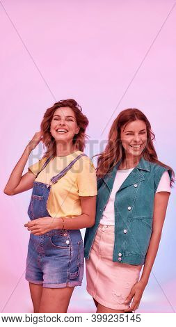 Two Joyful Attractive Young Girls, Twin Sisters Posing Together Isolated Over Pink Background. Famil