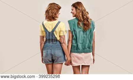 Back View Of Two Young Girls, Twin Sisters In Casual Wear Holding Hands, Looking At Each Other, Posi