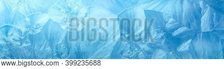 Wintry background with winter frost covered window with a pattern of ice crystals.