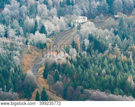 Railway Station Jedlova, Birds View. Early Winter Hoarfrost Cover Treetops. Cold And Misty Morning,
