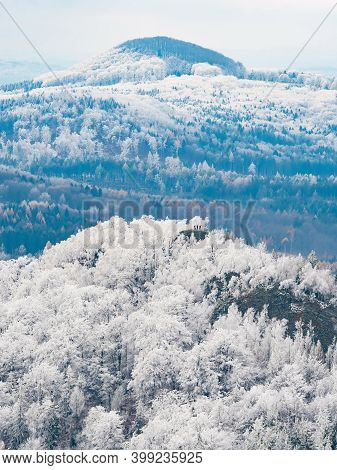Dark Blue Forest Hills Covered With Hoarfrost. Early Winter Freeze Weather. Hoarfrost On Treetops On