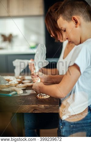 Mom And Children Decorate Christmas Gingerbread At Home. A Boy And A Girl Paint With Cornets With Su