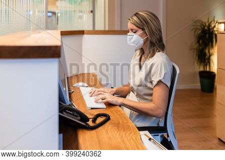 Young Woman At The Reception Of Fitness Club Or Health Centre With Mask