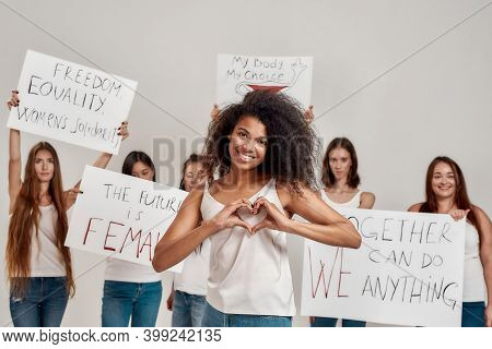 Young African American Woman Showing Heart Or Love Sign, Smiling At Camera. Group Of Diverse Women H