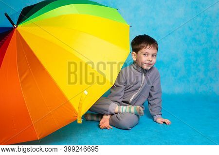 A Boy With A Colored Umbrella On A Blue Background . Summer Season. Umbrella From The Rain. Boy On A