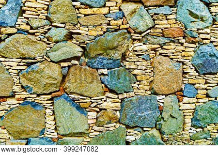 Ancient Stone Wall Made Of Natural Rough Stones, Old Masonry With Cement And Hewn Texture Of Stonewa