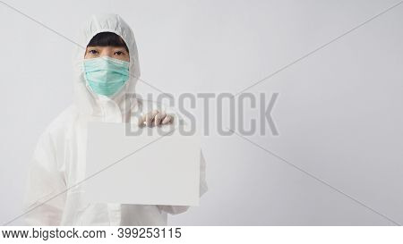 Female Model Wearing Ppe Suite And Face Mask And Two Hand With Gloves Is Holding A4 Paper On White B