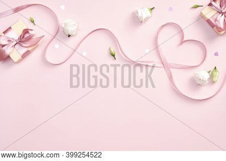 Ribbon In Shape Of Heart With Gift Boxes And Rose Flowers On Pink Background. Happy Valentines Day,