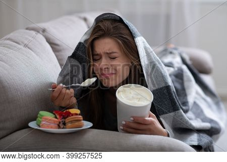 Upset Young Woman Dealing With Depression By Eating Ice Cream And Sweets Under Blanket On Sofa. Stre