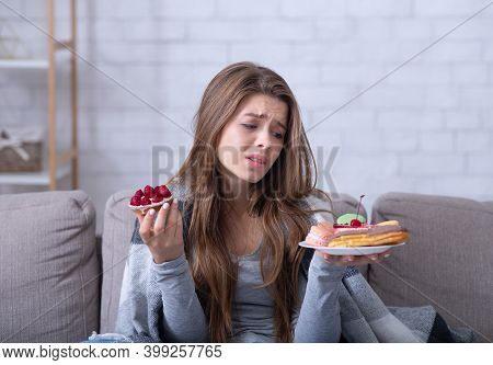 Depressed Young Lady Having Eating Disorder, Comforting Herself With Sweets On Sofa At Home. Unhappy