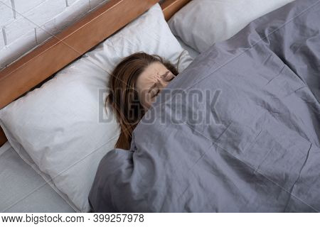 Mental Health Concept. Depressed Young Woman Hiding Under Blanket On Bed, Suffering From Depression,