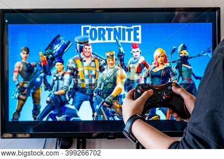 Woman Holding A Generic Controller And Playing Popular Video Game Fortnite On A Television And Pc