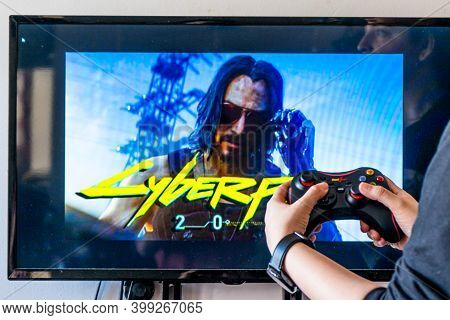 Woman Holding A Generic Controller And Playing Popular Video Game Cyberpunk 2077 On A Television And