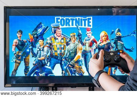 Woman Holding A Xbox Controller And Playing Popular Video Game Fortnite On A Television And Pc