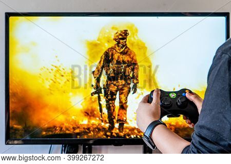 Woman Holding A Xbox Controller And Playing Popular Video Game Call Of Dutyon A Television And Pc