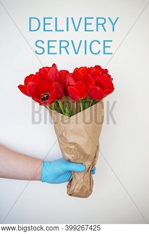 Contactless Delivery Of Disposable Gloves Of A Bouquet Of Red Tulips, The Concept Of Quarantine And