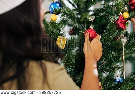 Young Woman In Santa Claus Hat Hanging Red Bauble On Christmas Tree