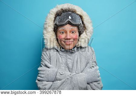 Winter Holidays And Recreation Concept. Cheerful Frozen Woman Feels Cold After Going Snowboarding In