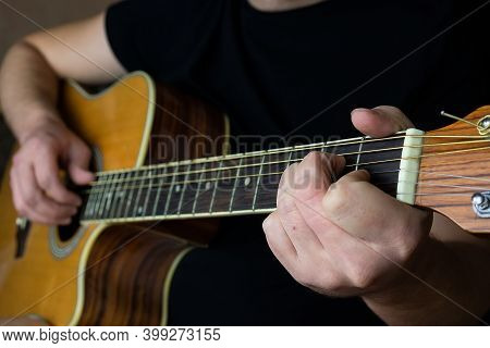 A Male Hand While Playing An Electro Acoustic Guitar. Close-up. Human Hand Plays Guitar. Guitar Play