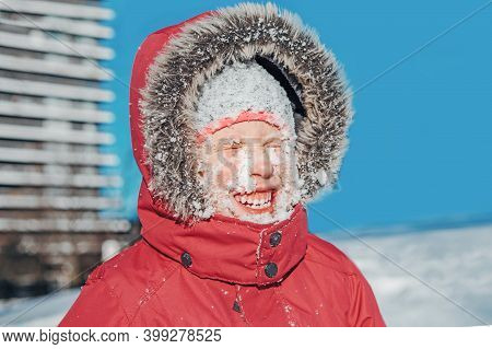 Funny Cute Adorable Caucasian Smiling Girl In Red Jacket Parka Squinting Eyes From Bright Sun. Happy
