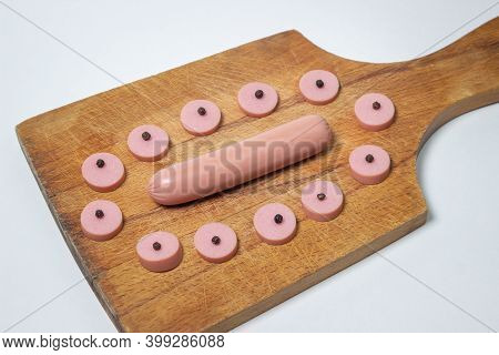 Sausages On A Wooden Board. Sliced Sausage Around A Whole Sausage. Meat Product On A White Backgroun