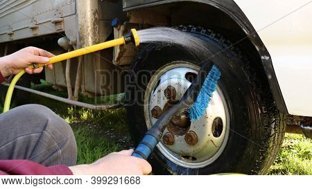 Male Hands Washing Truck Wheel Using Water Pressure From Yellow Hose And Blue Brush, Outdoor Car Was