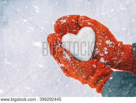 Female Hands In Knitted Mittens With Heart Of Snow In Winter Day. Love Concept. Valentine Day Backgr