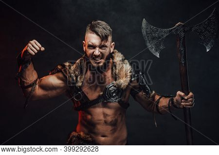 Nordic Barbarian With Lights Armour Showing His Huge Biceps Looking At Camera And Holding His Two Ha