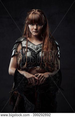 Beautiful Northern Amazon In Dark Armour With Huge Axe Posing In Dark Background.
