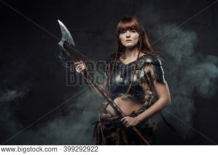 Portrait Of Warlike Female Fighter From North With Long Brown Hairs In Dark Armour With Two Handed A
