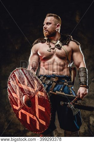 Serious And Wild Viking With Muscular Build And Naked Torso Holding Shield And Hatchet In Dark Backg