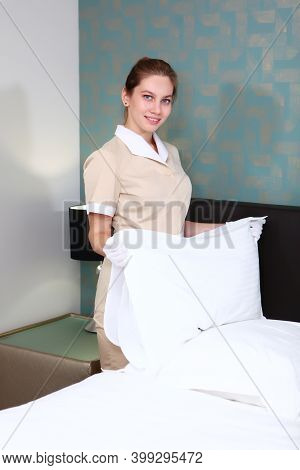 Pillow In The Hands Of The Maid. Cleaning In A Hotel Room. A Maid In Uniform And White Gloves. The C