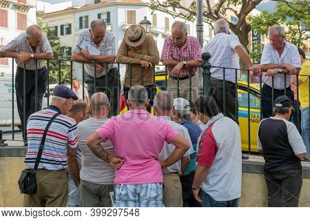 Funchal At Madeira, Portugal - August 01, 2014: Group Of Older Men Looking To Two Man Playing Cards