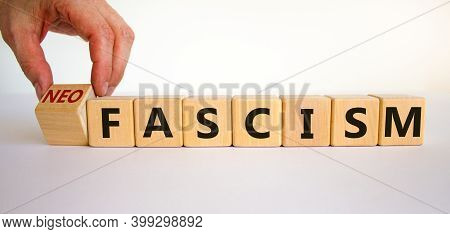 Neofascism Symbol. Man Hand Turns A Cube And Changes The Word Fascism To Neofascism. Business And Fa