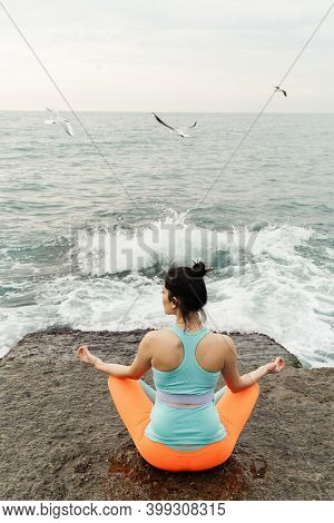 Young Woman Doing Yoga By The Sea, Seagulls Flying Around, Meditation. High Quality Photo